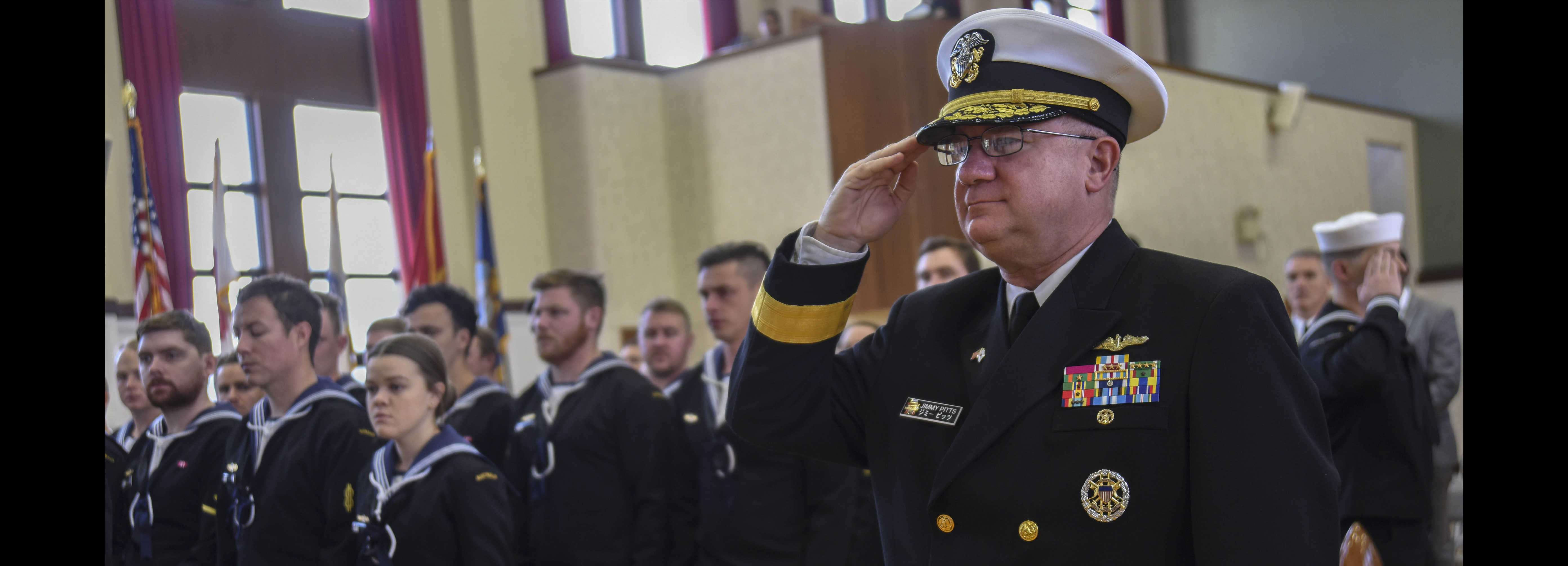 Rear Adm. Jimmy Pitts, Commander, Submarine Group 7, salutes during the national anthem prior to giving the keynote address at the Fleet Activities Yokosuka