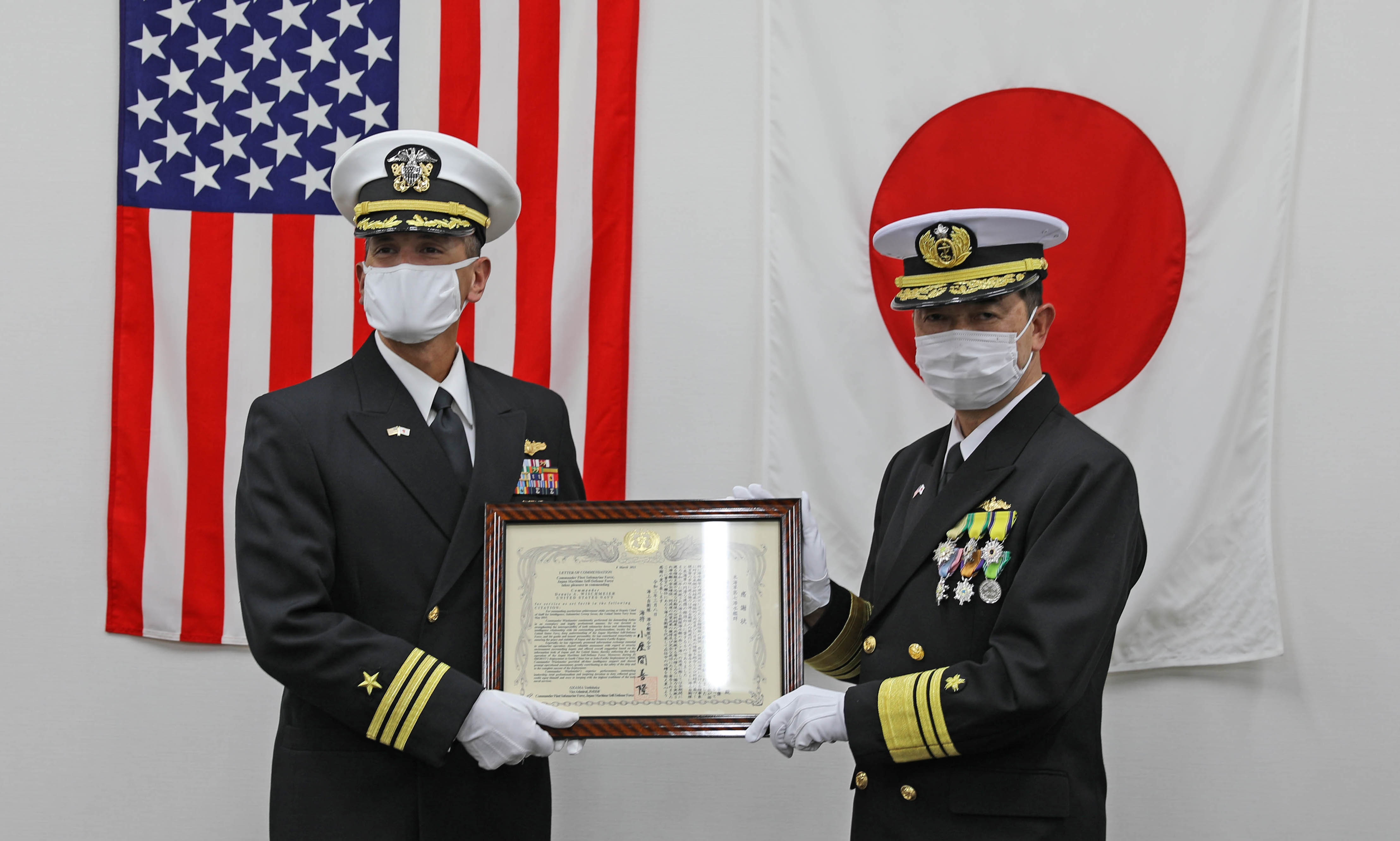 210308-N-DS193-0046 Taura, Japan (March 8, 2021) – Vice Adm. Yoshitaka Ozama, Commander, Japan Maritime Self-Defense Submarine Force, presents Commander Submarine Group 7's Intel Deputy Chief of Staff, Cmdr. Dennis Wischmeier with the Defense Cooperation Award Second Class for his distinguished achievements and contribution to the defense cooperation between Japan and United States.  America never fights alone, and we are far stronger when we stand alongside our allies and partners to uphold free and open conditions at sea.