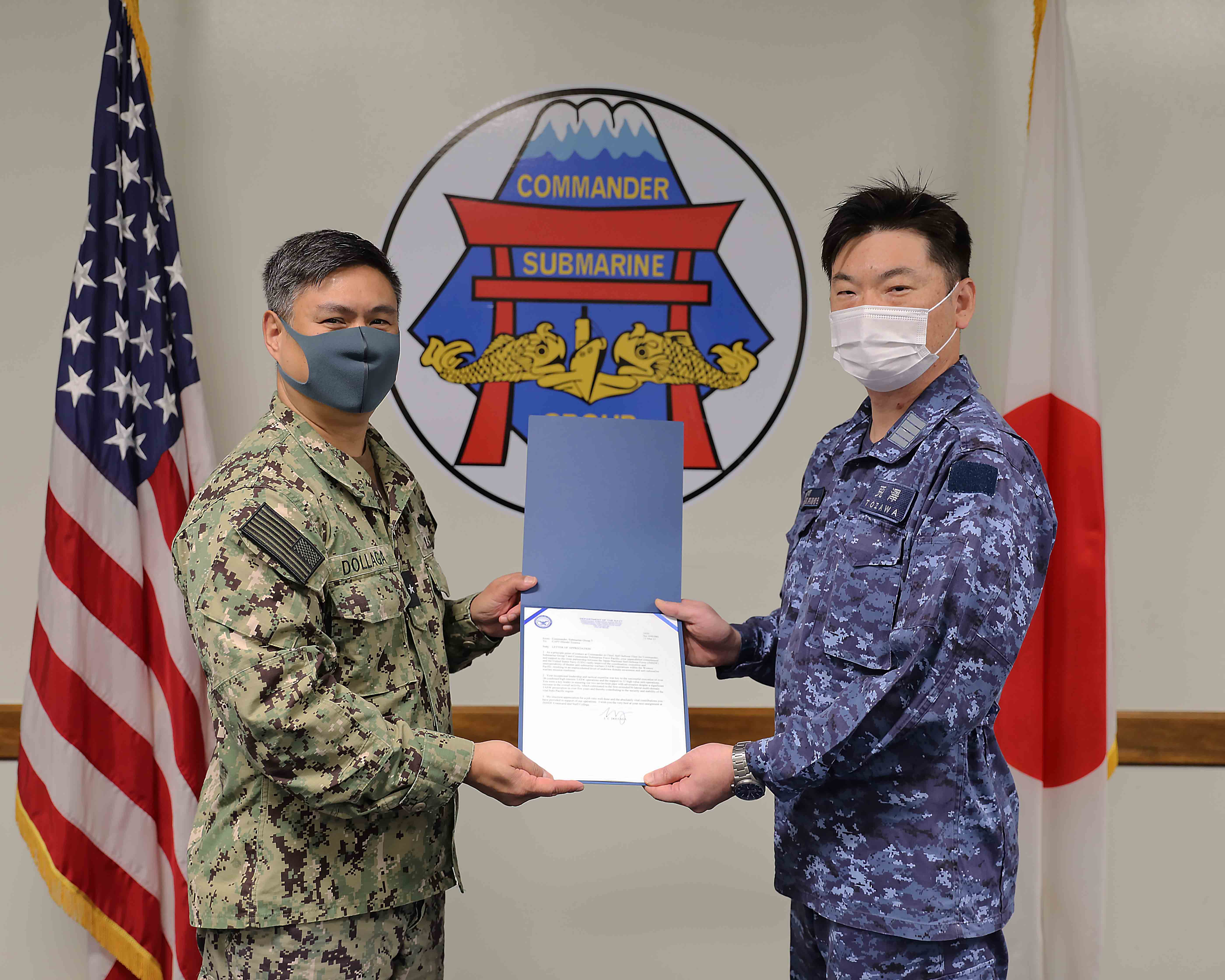 210315-N-DS193-0004 YOKOSUKA, Japan (March 15, 2021) - Rear Adm. Butch Dollaga, Commander, Submarine Group 7, presents Lt. Cmdr. Satoshi Koisumi with a letter of appreciation for his unparalleled commitment and support to the close partnership between the Japan Maritime Self-Defense Force and U.S. Navy.