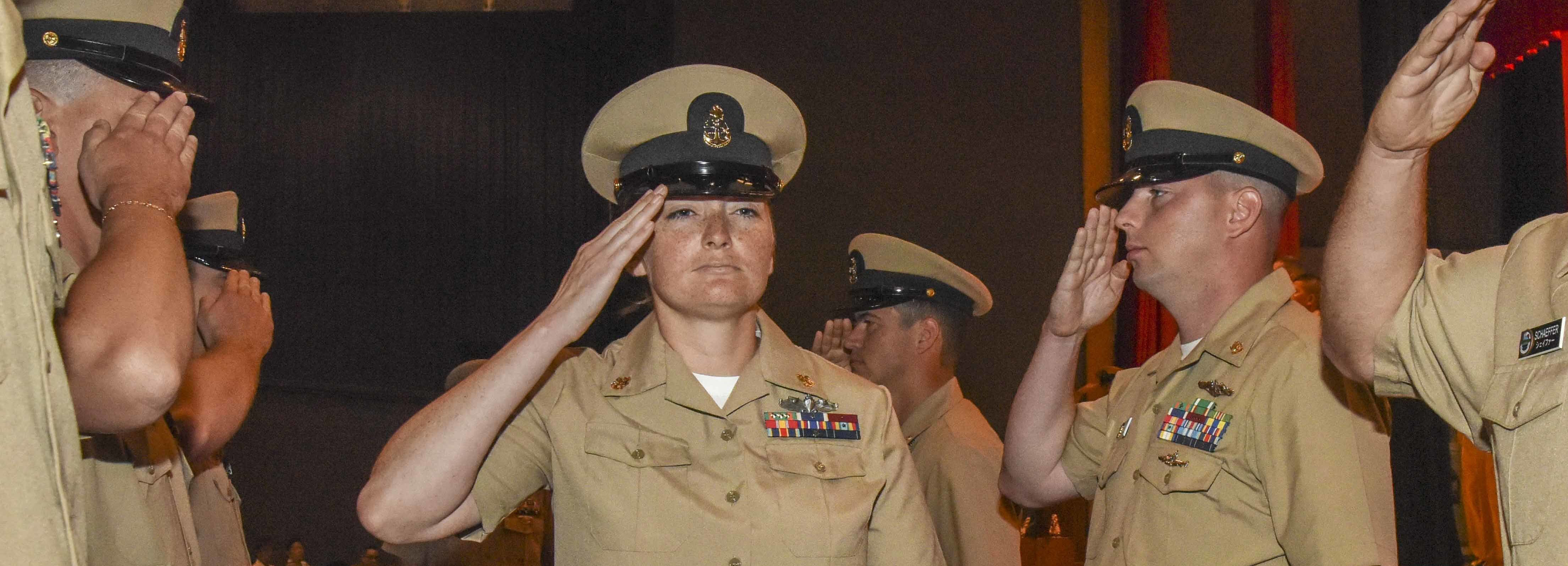 Chief Firecontrolman Gina Champion from Tucson, Arizona, assigned to Commander, Submarine Group 7, salutes as she walks through sideboys during a chief petty officer pinning ceremony at the Fleet Theater. Fourteen Sailors from five commands across Fleet Activities Yokosuka were advanced to chief during the event.