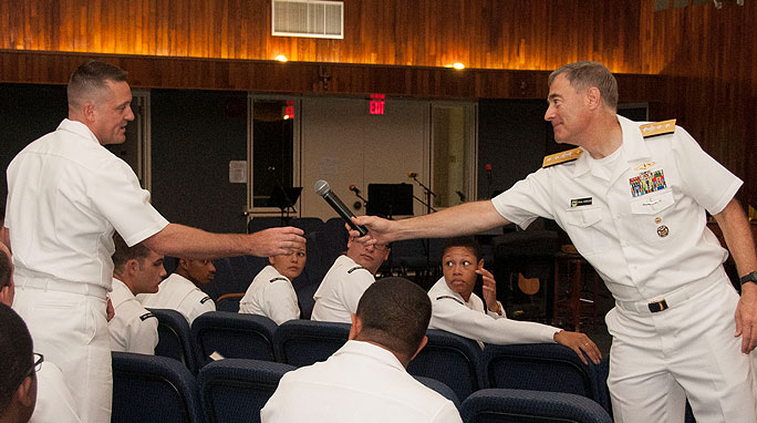 RADM Roegge passes the microphone to a sailor during a town hall meeting.